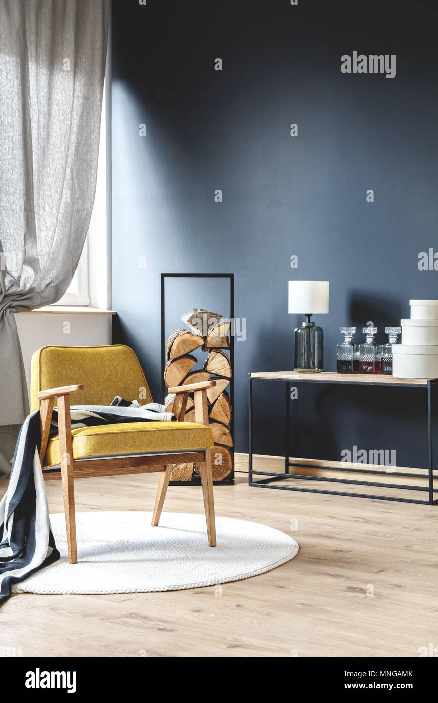 Wooden yellow armchair with blanket standing on white rug in stylish living room with wood logs, black wall and gray curtains Stock Photo