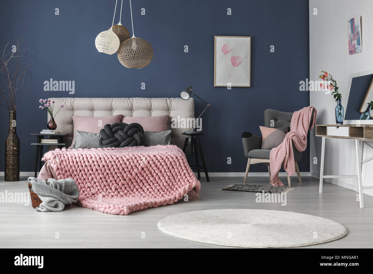 Dark grey comfy armchair with cushion and pink blanket in the corner of the room - Stock Image