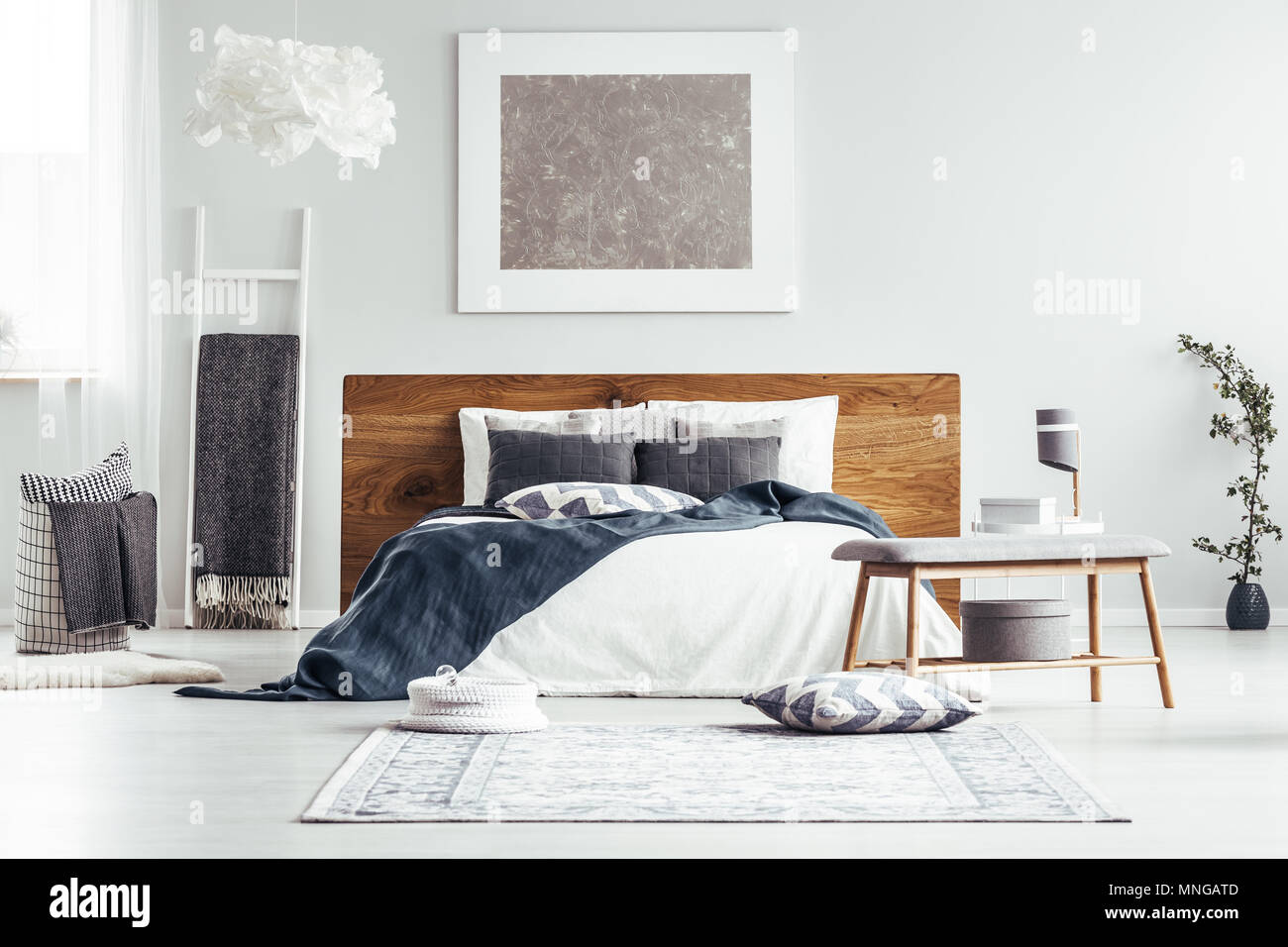 Silver Painting On White Wall Above Bed In Designer Bedroom Interior With Ladder Lamps And Bedsheets Stock Photo Alamy