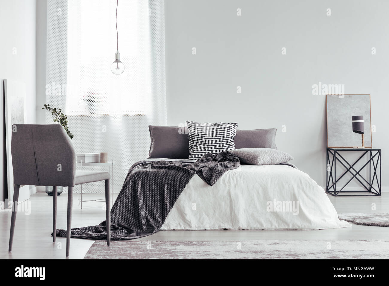 Grey chair and bed with patterned cushions and blanket in ...