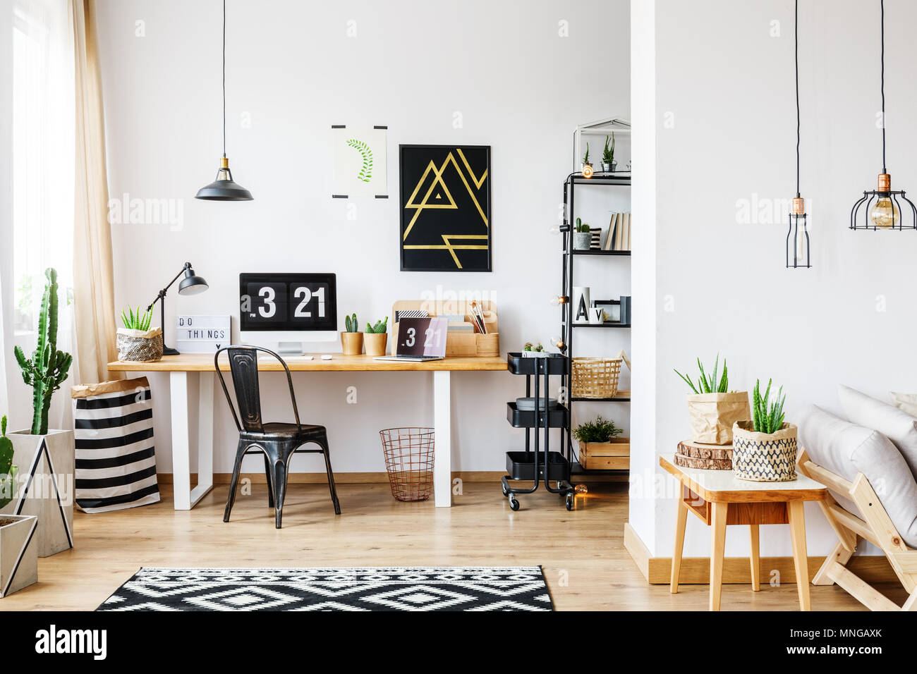 Trendy room with workspace for a freelancer with white wall, desk, black vintage chair, industrial lamps, poster and wooden sofa in bright open living - Stock Image