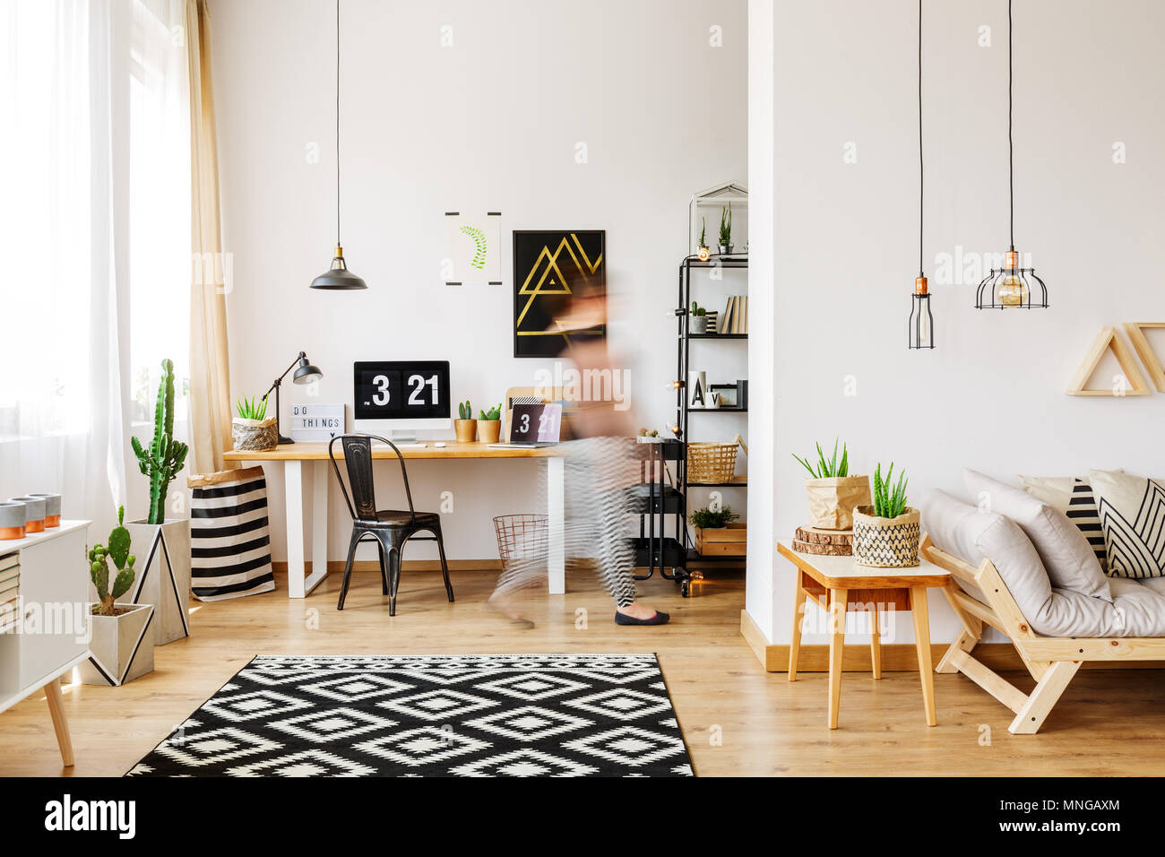 Home furniture of a freelancer with natural eco accessories, wooden desk, potted plants, patterned rug, computer and triangle shelves in spacious livi - Stock Image