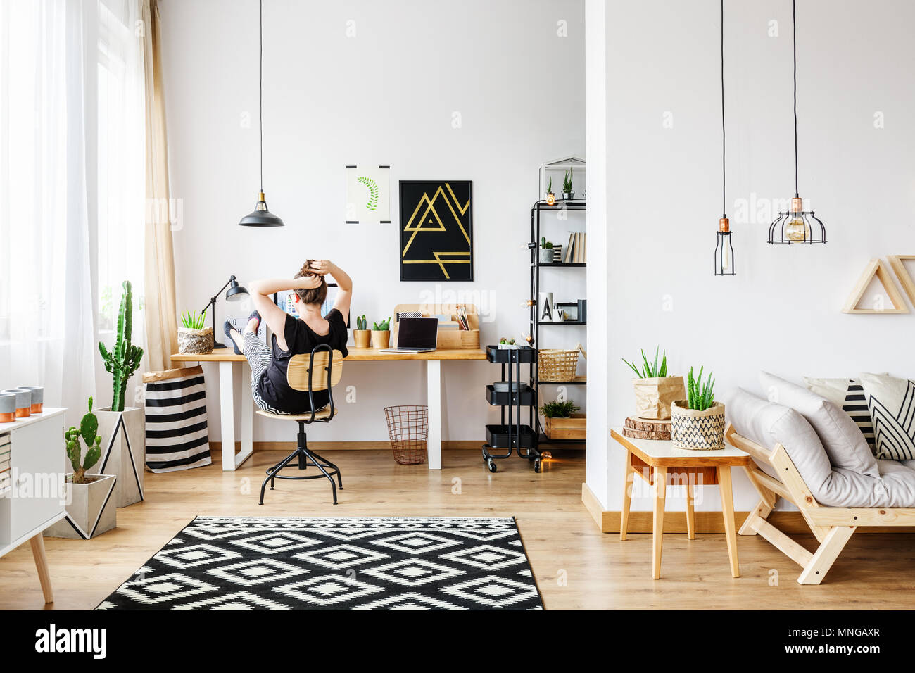 Young freelance woman working remotely at designer home in cozy white office room with pendant lamps, white wall, big window, comfy couch and aloe pla - Stock Image