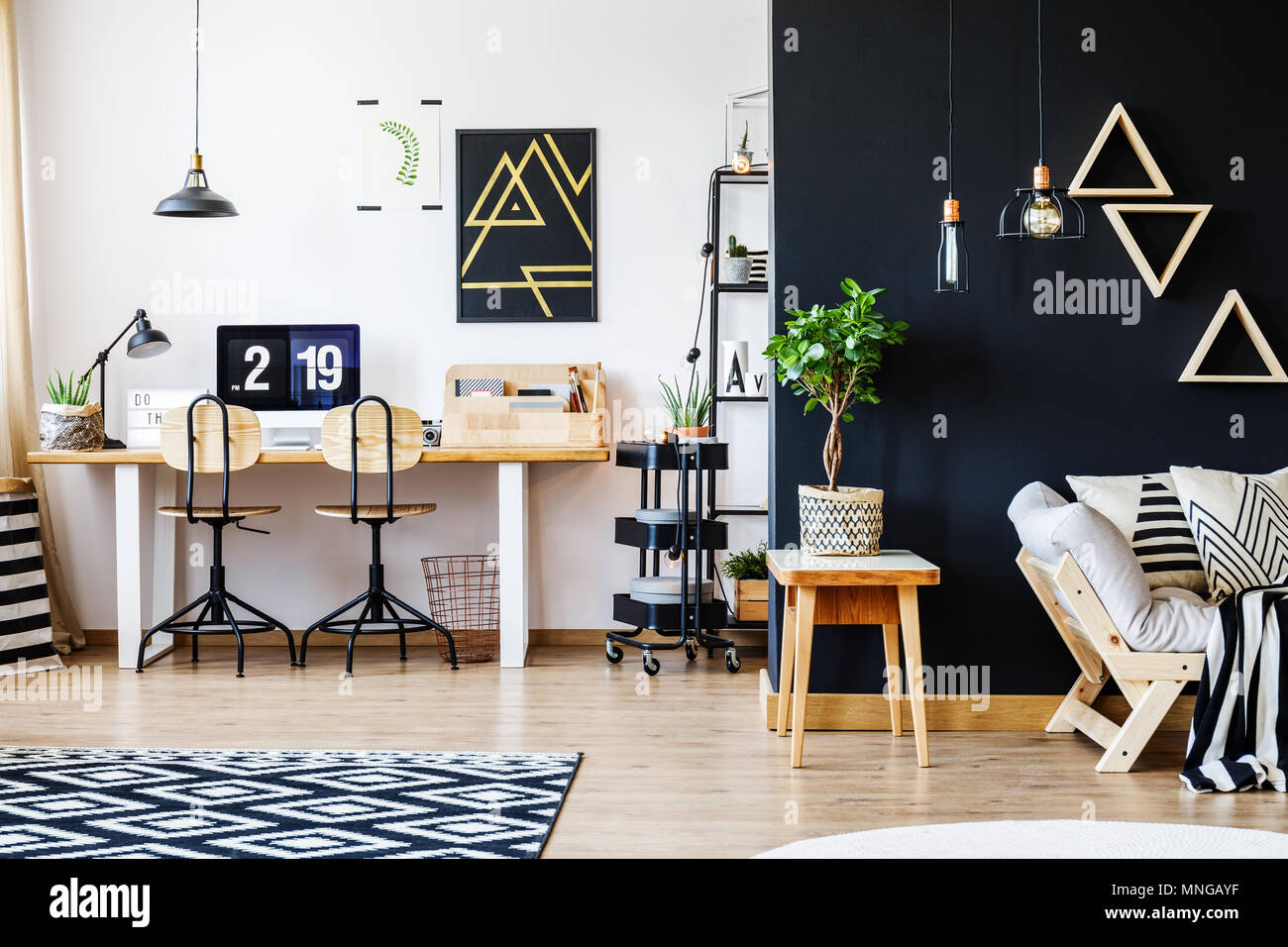 Stylish black and white nordic style open space apartment with wooden furniture, office workspace with desk and computer, and spacious living room wit - Stock Image