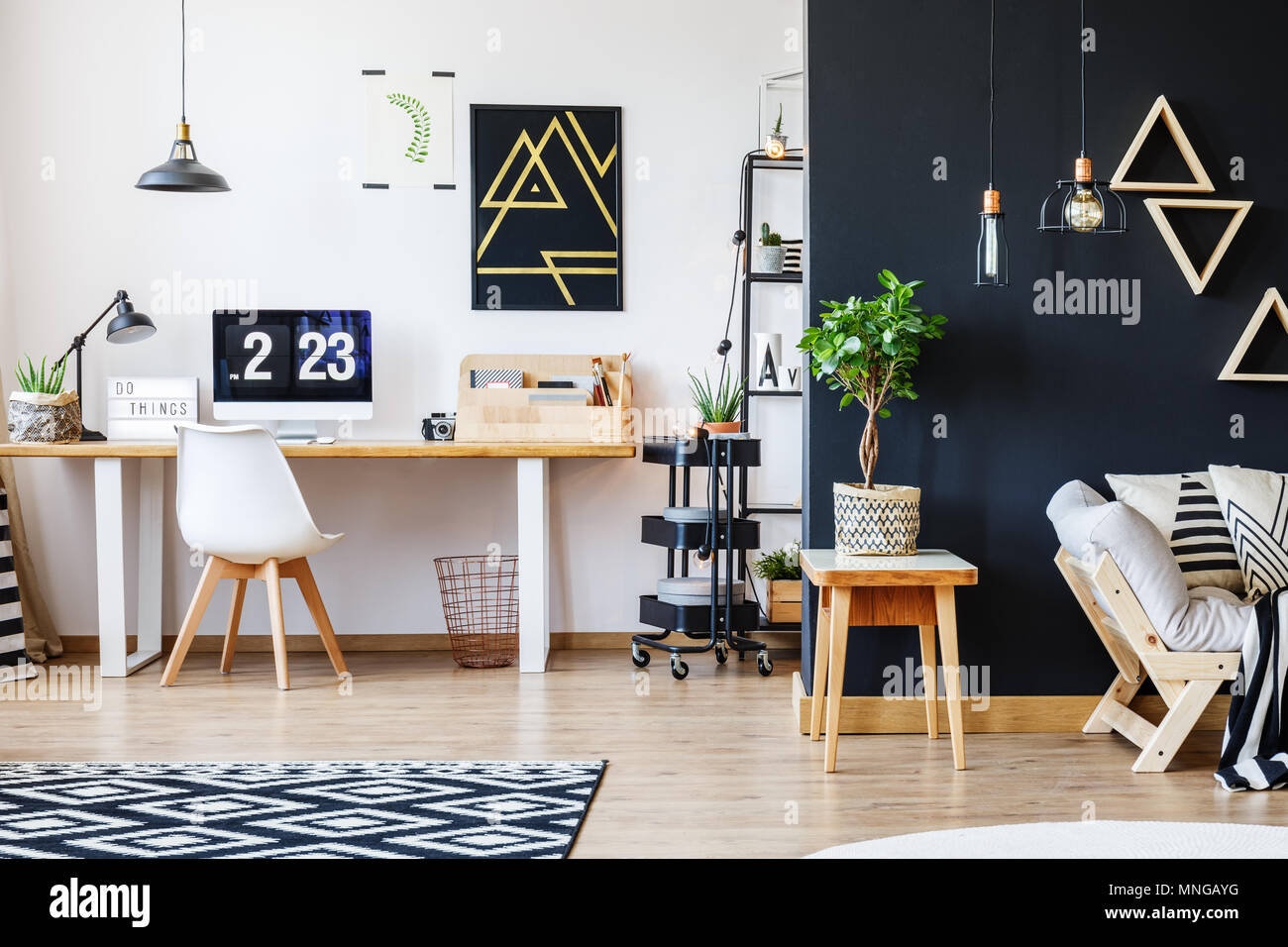 Nordic natural interior in stylish open studio for a freelancer with sofa, black wall and office space with desk and black accent - Stock Image