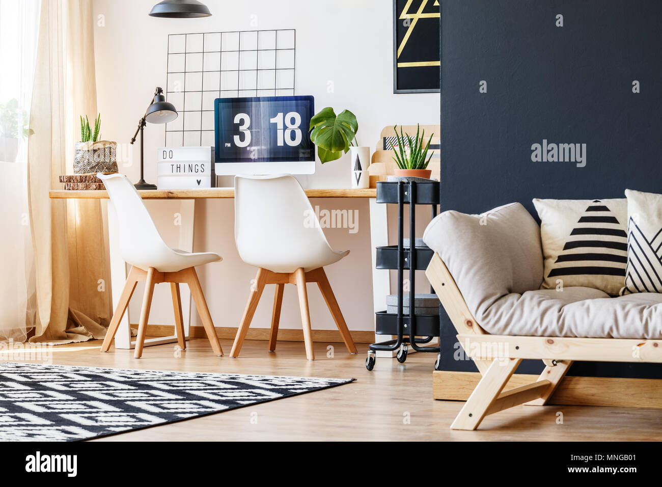 Side angle view of trendy, open space interior with modern nordic office area with desk, aloe plant, computer and cozy living room with wooden sofa, b - Stock Image