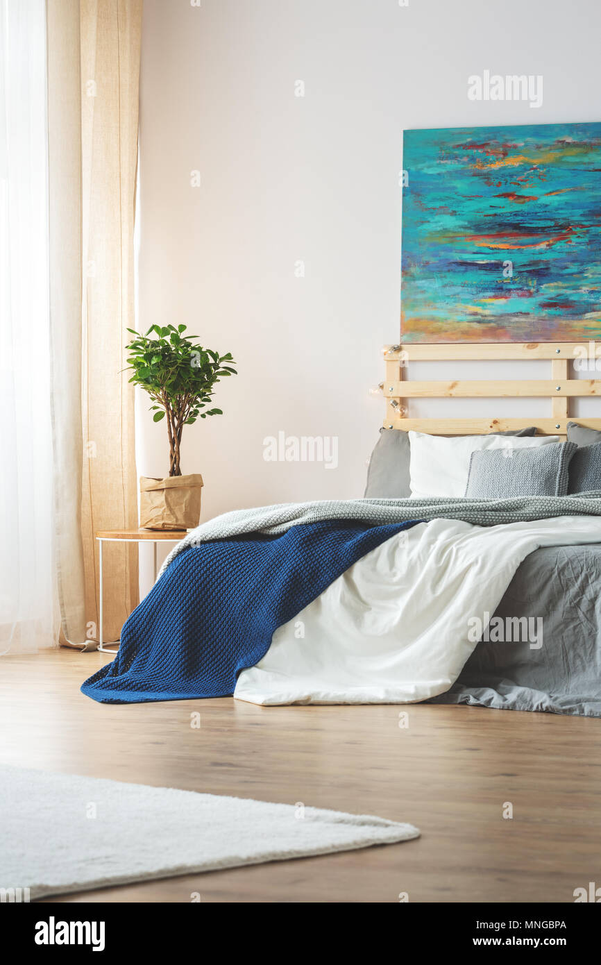 Modern bedroom with blue painting above king-size bed Stock ...