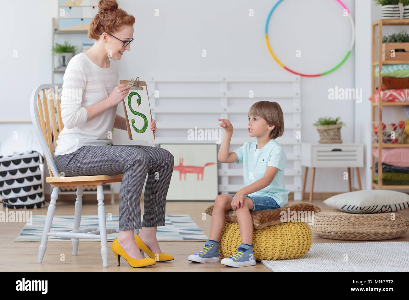 Boy sitting on a yellow pouf practicing correct