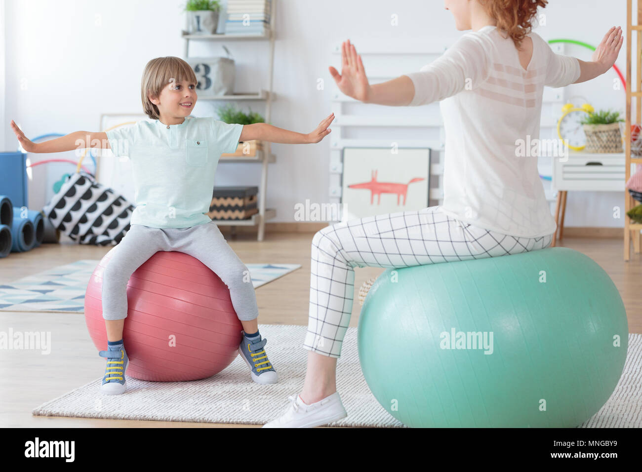 Physiotherapist and young boy doing stretching exercise on colorful balls in bright room - Stock Image