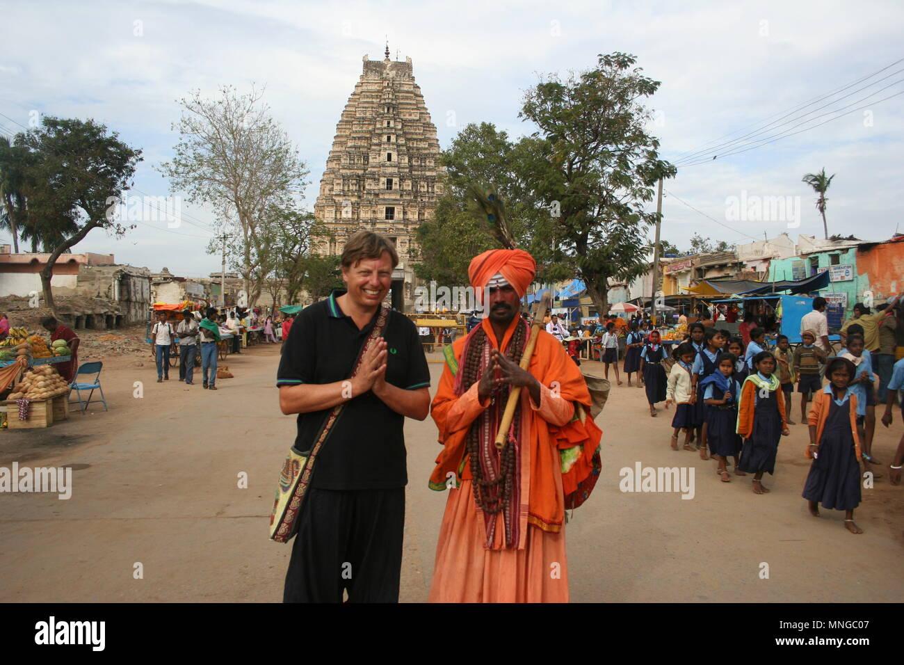 Holy Man, Tourist and Indian Schoolkids outside VirupakashaTemple, Hampi - Stock Image