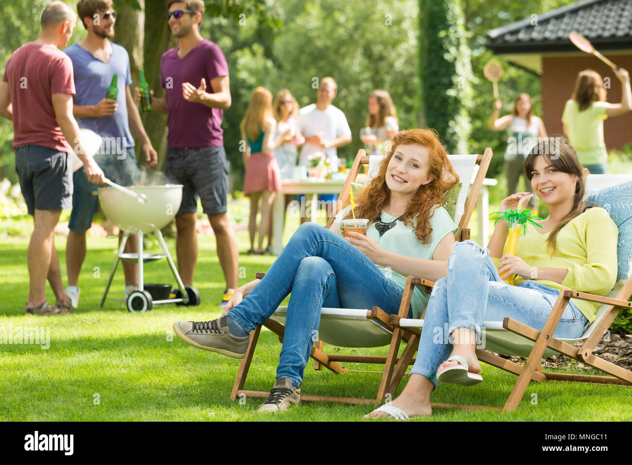 Two girls sitting on deckchairs with drinks, men grilling Stock Photo