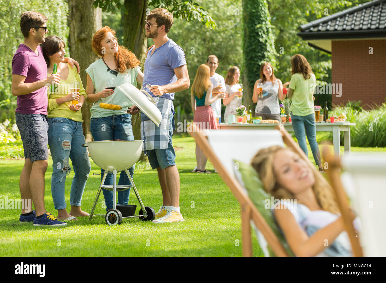 Young man grilling food while talking with friends Stock Photo
