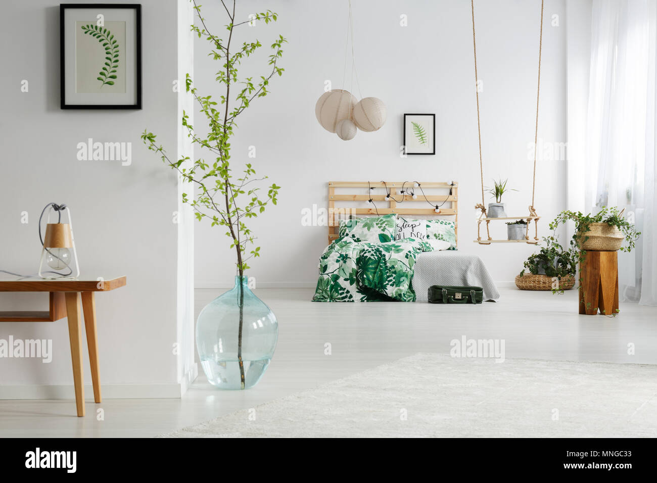 White bedroom with green plants, wooden bed and swing Stock Photo ...