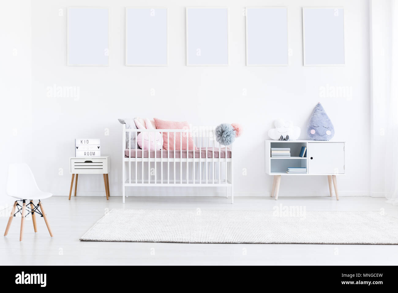 Gallery of mockups of white posters in girl's bedroom with small white chair and pink pillows on bed Stock Photo