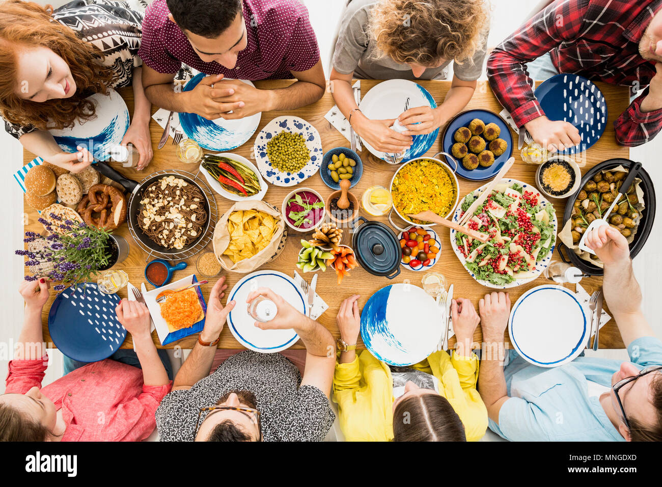 Red haired woman and her friends enjoy vege meeting with healthy food Stock Photo