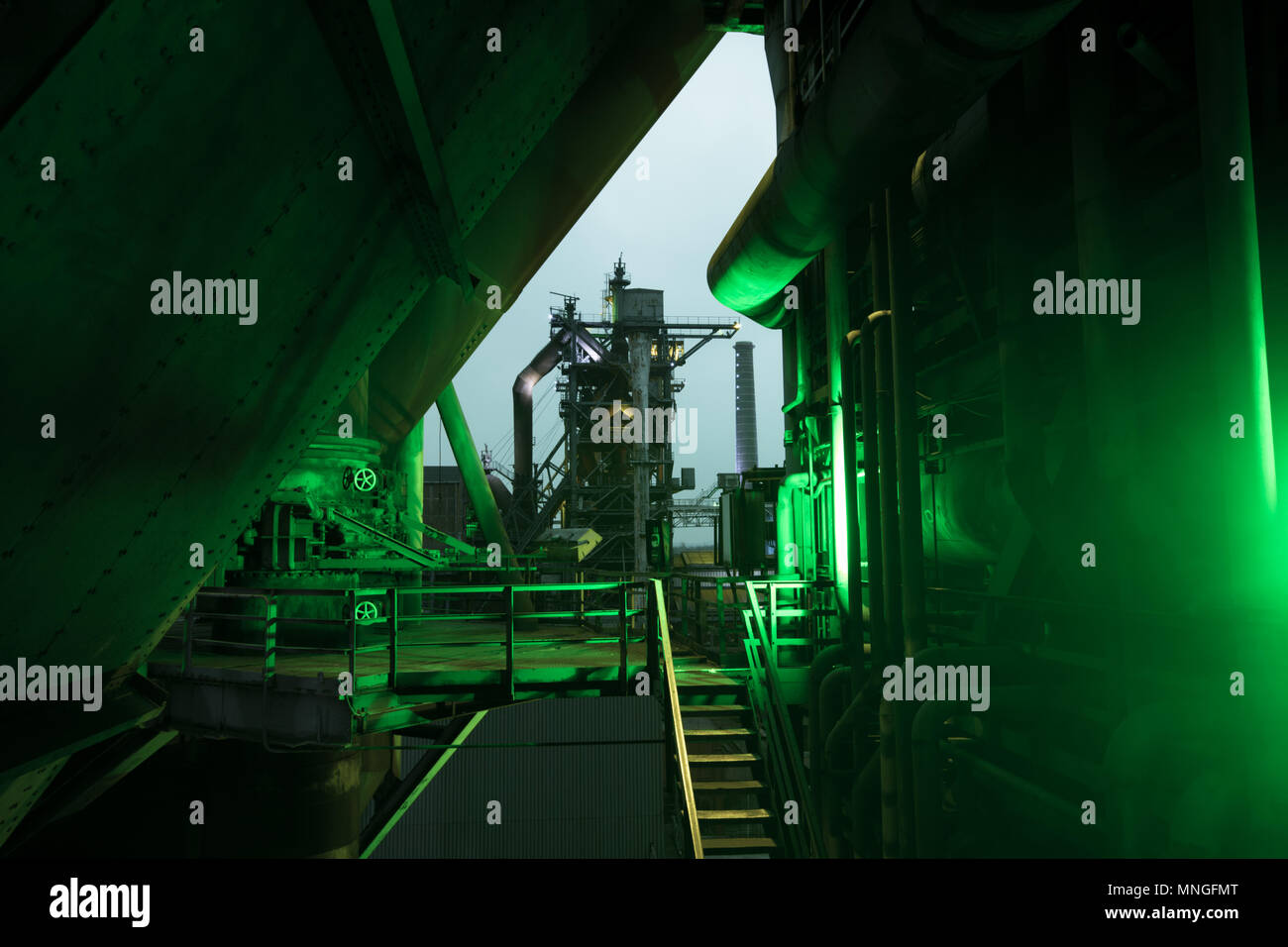 Night view of a historical steel factory in duisburg, germany, with a green lamp, shining from the side, in the foreground Stock Photo