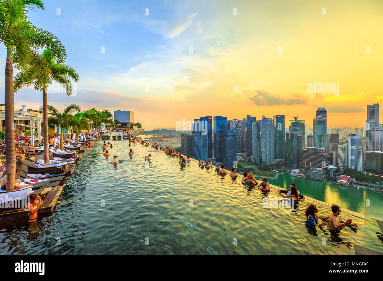 Singapore - May 3, 2018: Infinity Pool at sunset of Skypark that tops the Marina Bay Sands Hotel and Casino from rooftop of La Vie Club Lounge on 57th - Stock Image