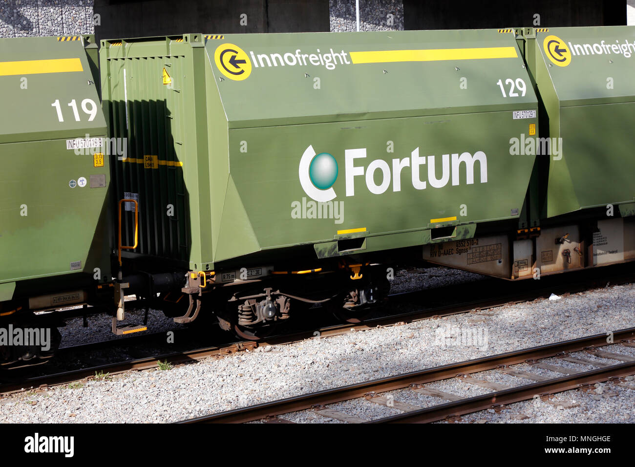 Stockholm, Sweden - May 16, 2017: Green railroad container freight cars of class Sgnss with containers intended for transport of wood chips as fuel ne - Stock Image