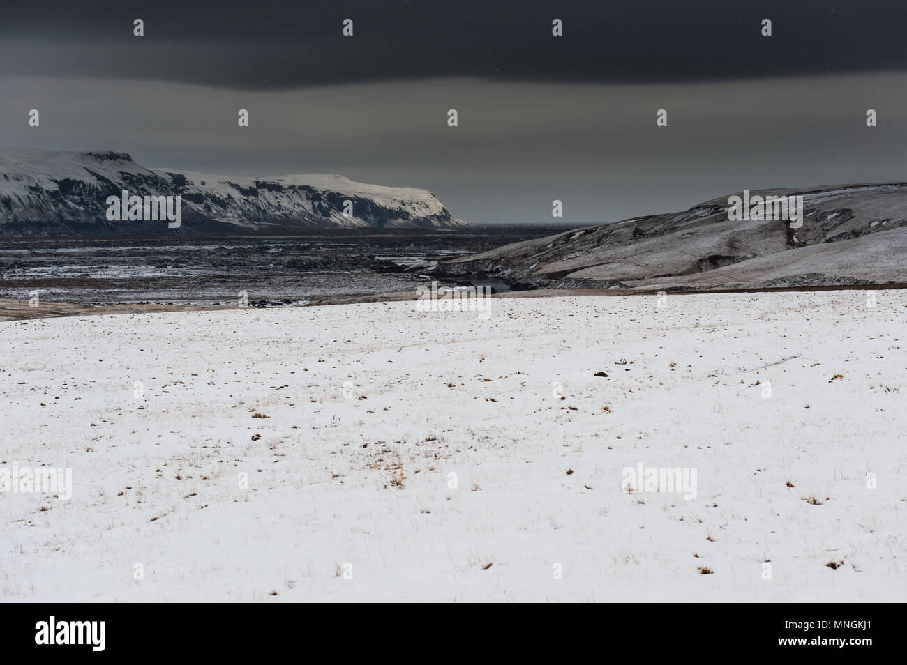 Melancholic landescape with cloud covered sky and snowfall in the icelandic back country, april 2018 - Stock Image