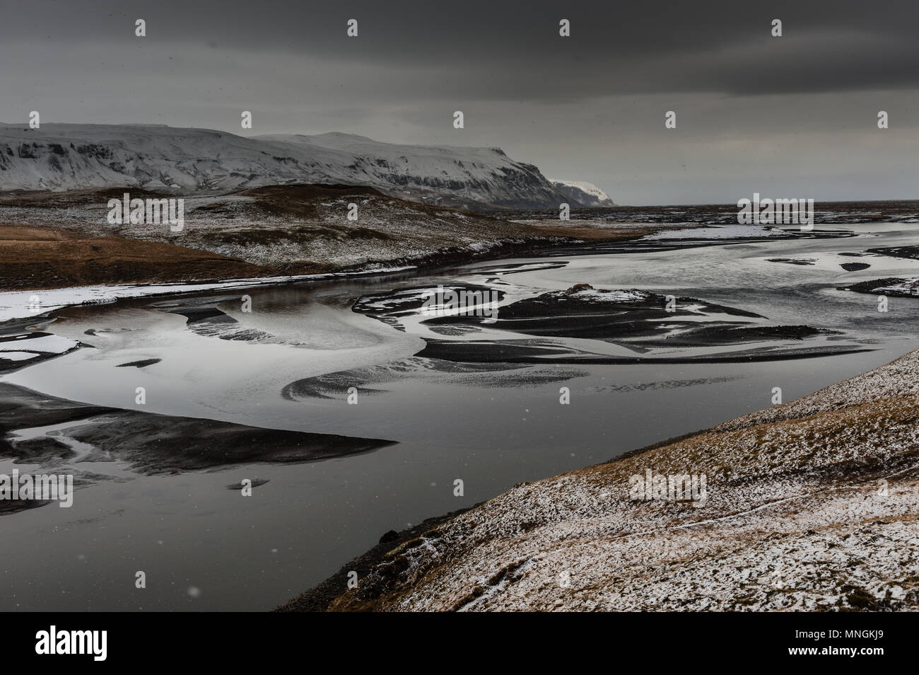 smowy weather with dark cloud covered sky at a black sanded riverbed in the icelandic back country, april 2018 - Stock Image
