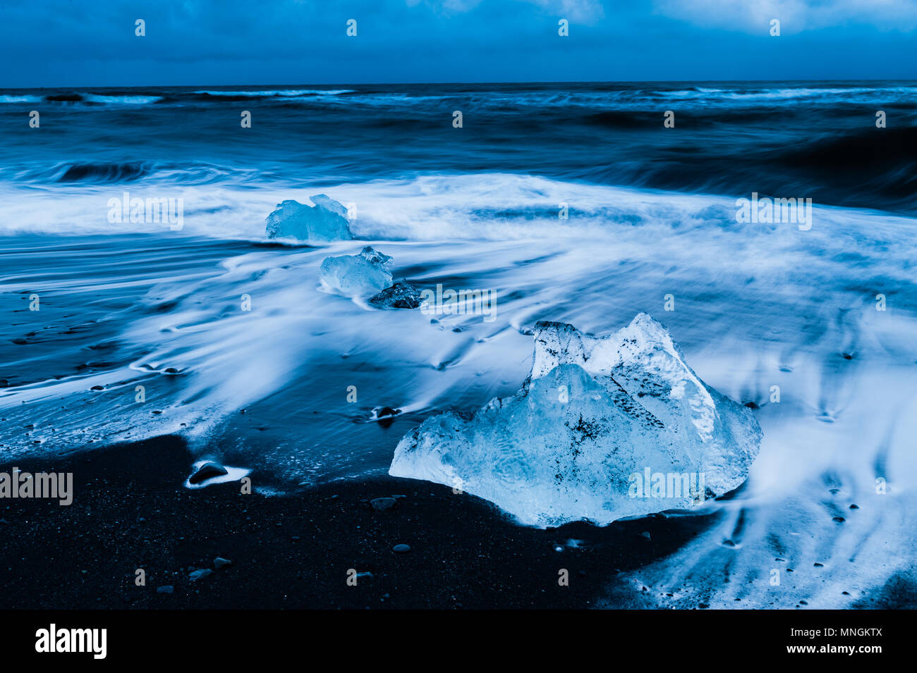 Ice rocks washed by the upcoming surf of the atlantic ocean at black volcanic sand at diamond beach, Iceland april 2018 Stock Photo