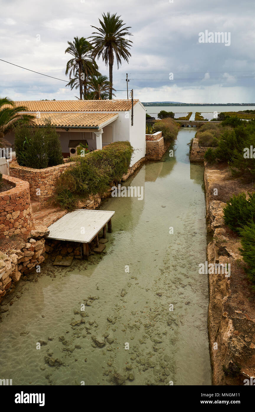 View of Sa Séquia water channel which communicates the Estany Pudent lagoon and the Mediterranean Sea in Formentera (Balearic Islands, Spain) - Stock Image