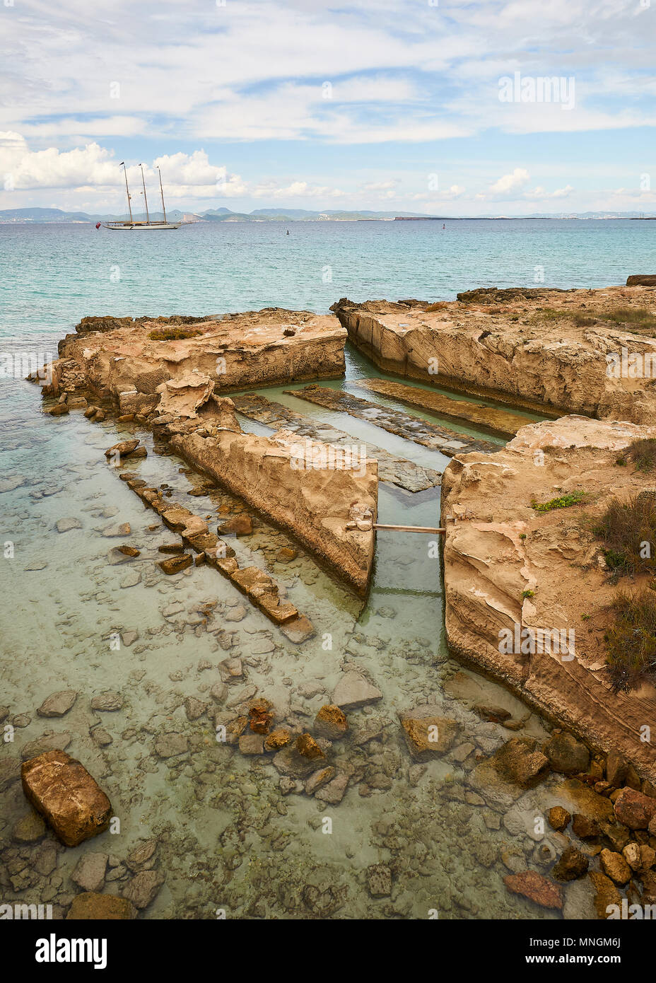 View of the vivarium built in the entrance of Sa Séquia water channel with a classic sailboat with Red Ensign flag (Formentera,Balearic Islands,Spain) - Stock Image