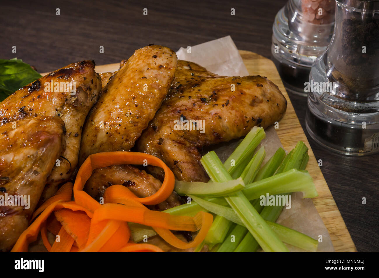 Fried chicken wings with sauce and salad - Stock Image