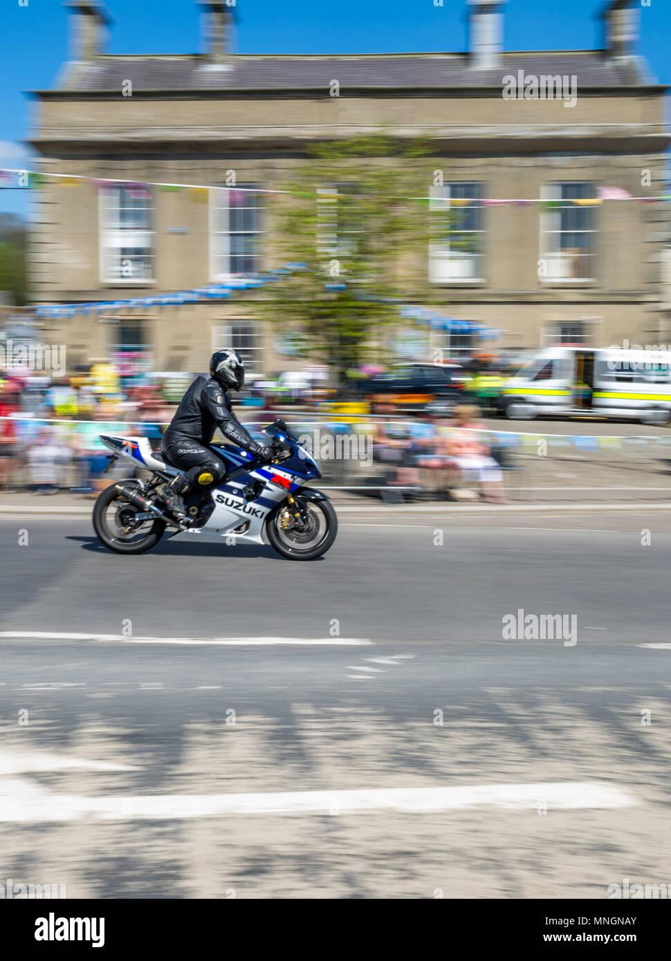 Suzuki motorbike being ridden through a yorkshire market town. - Stock Image