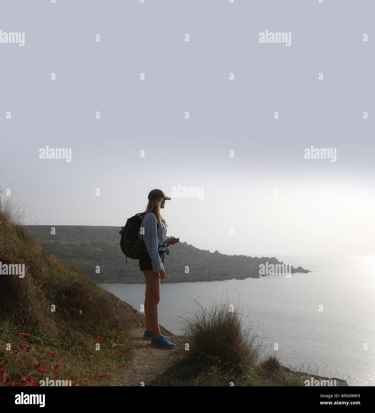 Young woman standing looking out to sea, she is wearing shorts a rucksack and peak cap. She is high up looking down - Stock Image