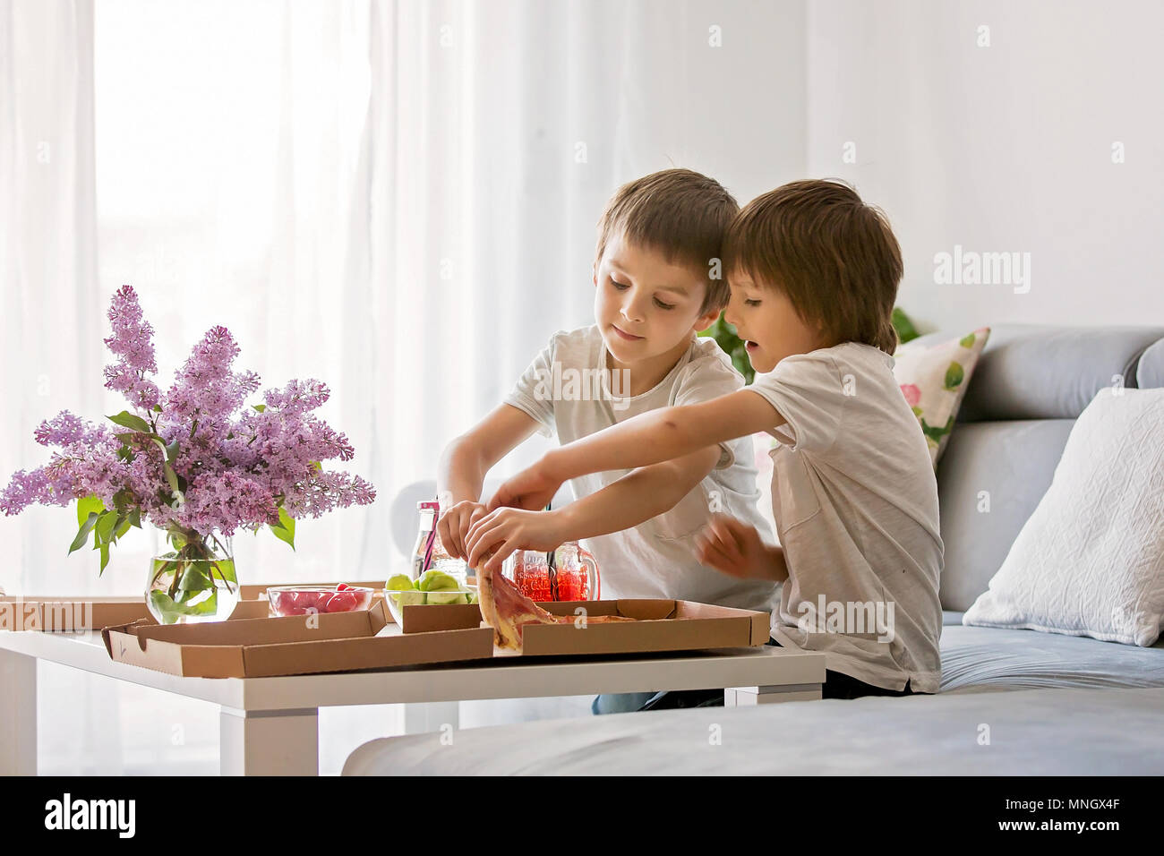 Beautiful young family with children, eating pizza at home and watching TV on a sunday - Stock Image