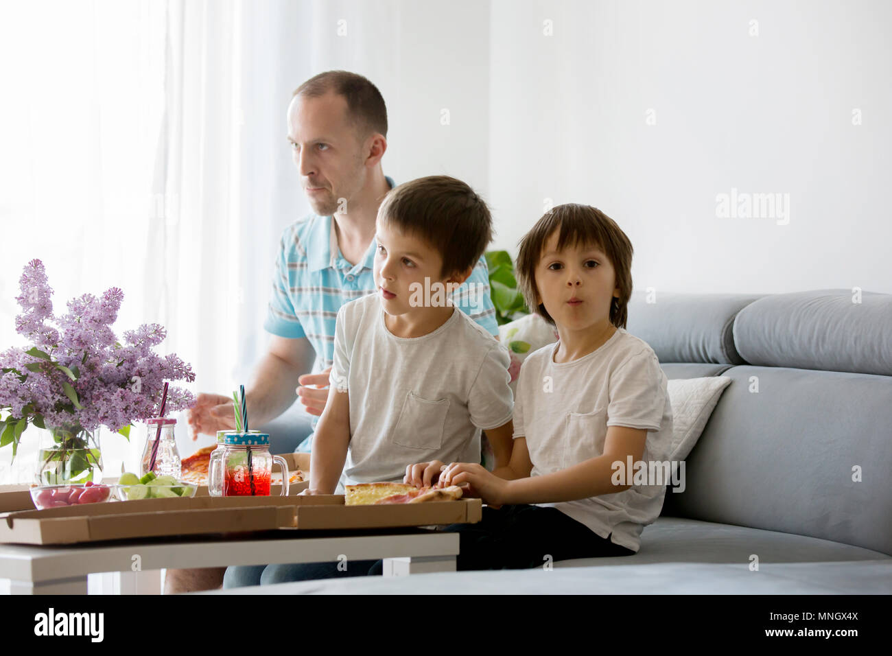 Father and his two boys, children, eating pizza at home and watching TV on a sunday - Stock Image
