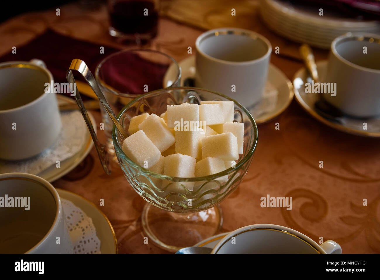 Close up vase with lumps of white sugar on table with cups. Tee time concept - Stock Image