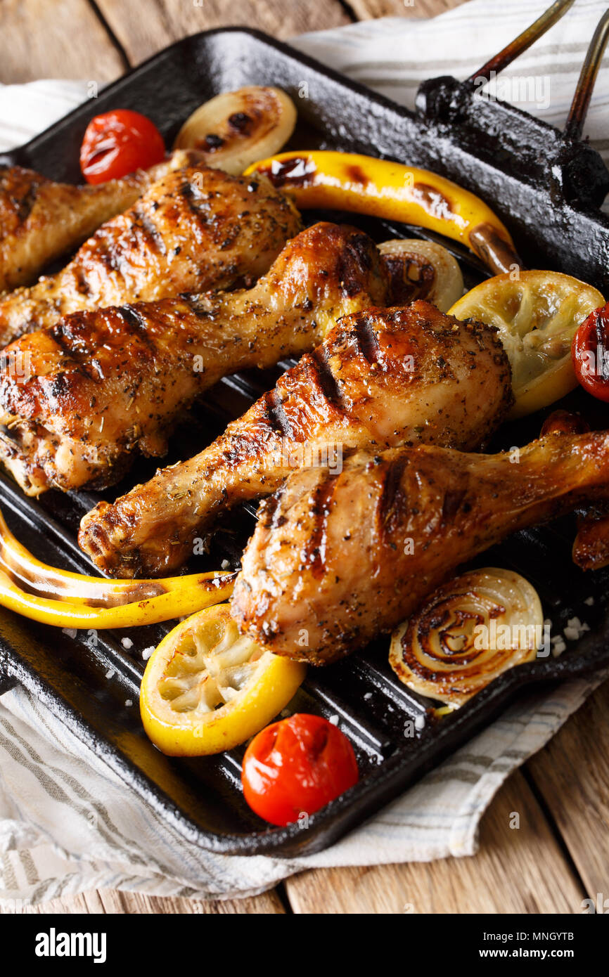Fried chicken drumstick with vegetables in a grill pan close-up on a table. vertical - Stock Image