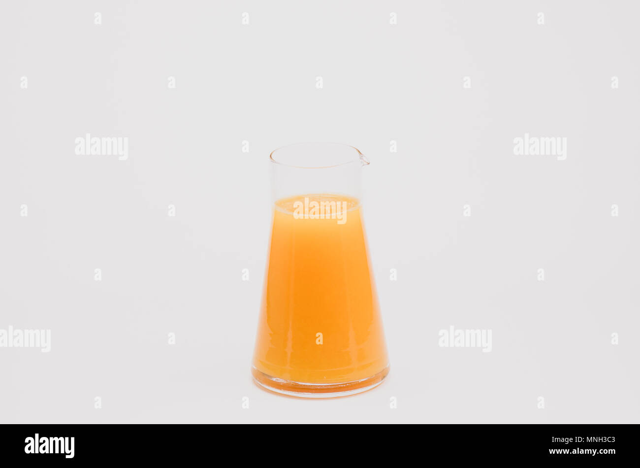 freshly squeezed oranges in a glass - white background - Stock Image
