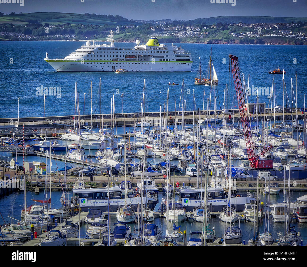 Torbay, UK . 17th May 2018. GB - DEVON: MS Hamburg arrival in Torbay with Torquay harbour in foreground. MS Hamburg is a 15,000-ton, 420 passenger, luxury cruise ship owned by the Conti Group and is now operated by Plantours Kreuzfahrten. UK 17. May 2018 Credit: nagelestock.com/Alamy Live News - Stock Image