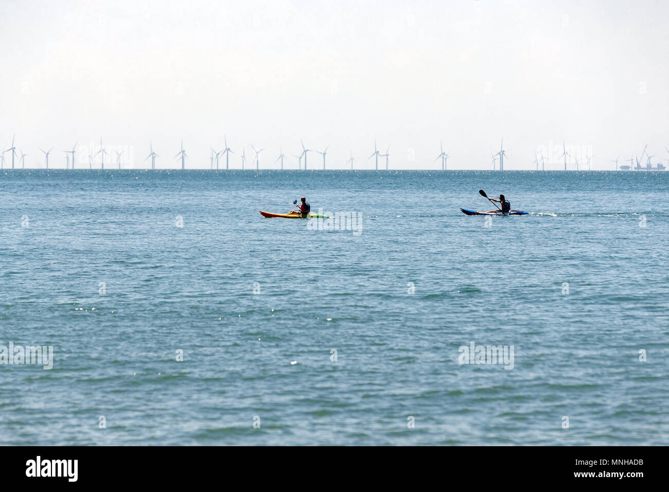 Two men with paddle boards in the sea. Paddleboards, paddleboarding, line of wind turbines. Brighton, East Sussex, UK. - Stock Image