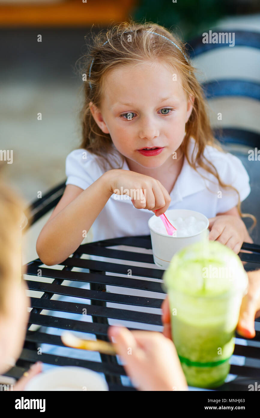 Little girl eating ice cream at outdoor cafe - Stock Image