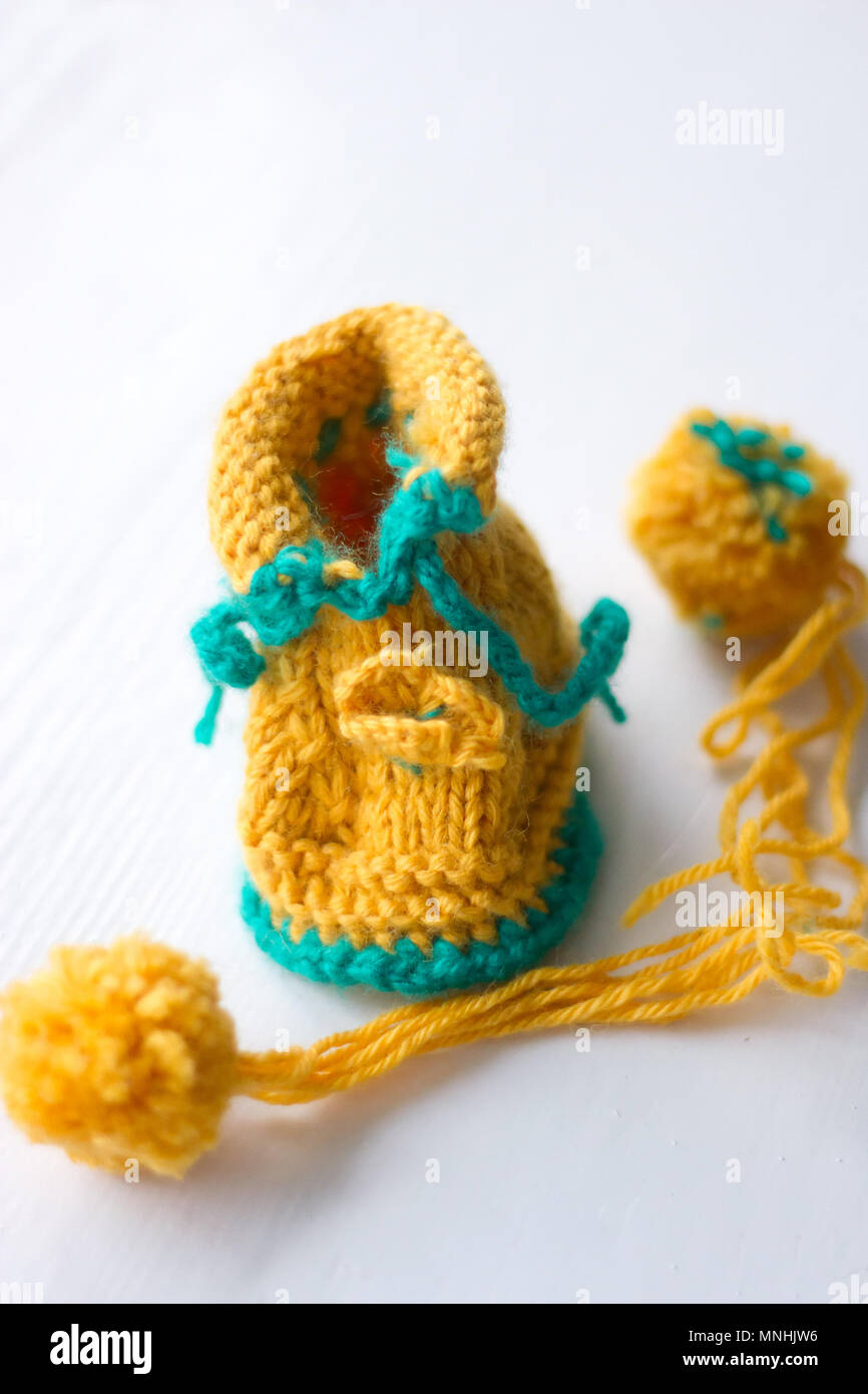 Knitted booties and a ball - Stock Image