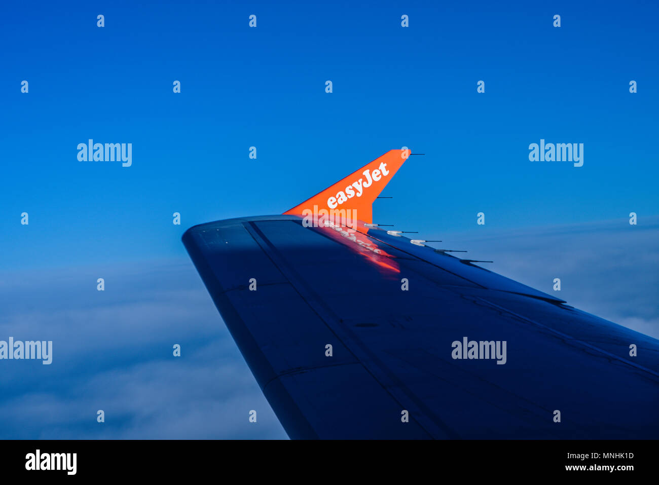 easyJet letering logo on jet plane wingtip winglet at dawn picked out by rising sun. Wing in shadow. Above clouds in blue sky. Airline, airliner - Stock Image