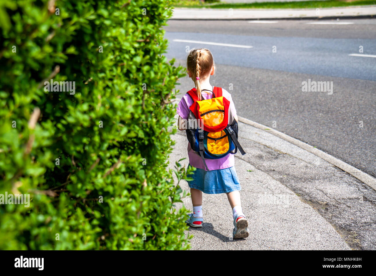 Little girls walking away with her filled backpack. - Stock Image
