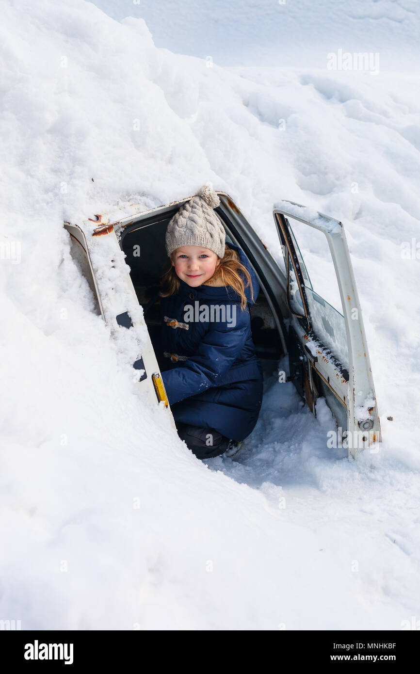 Adorable little girl outdoors on beautiful winter day in a car cover with snow after heavy snowfall Stock Photo