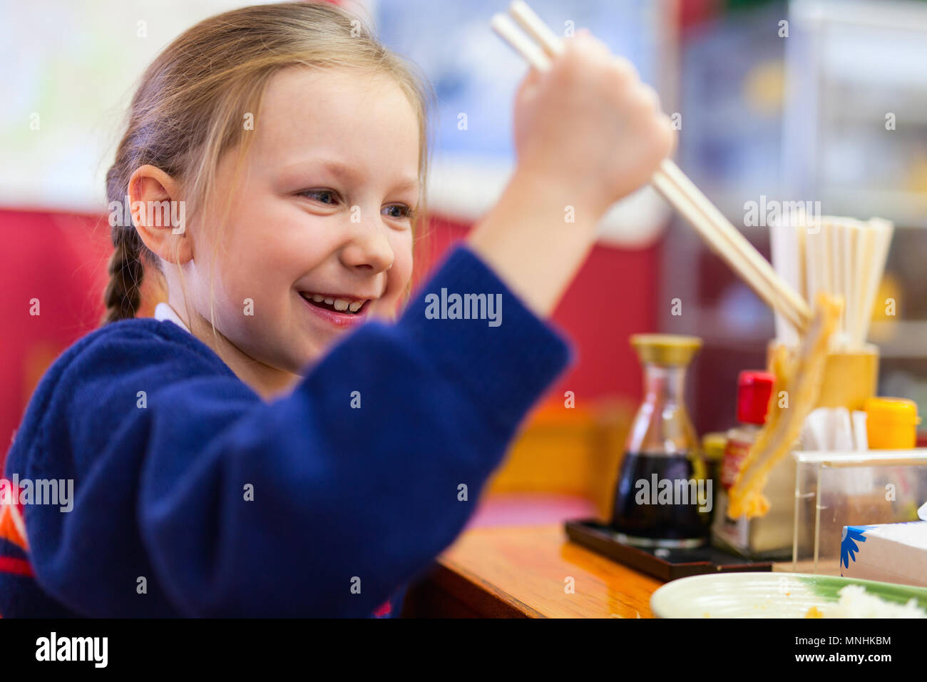 Portrait of adorable little girl playing with chopsticks at Japanese  restaurant - Stock Image