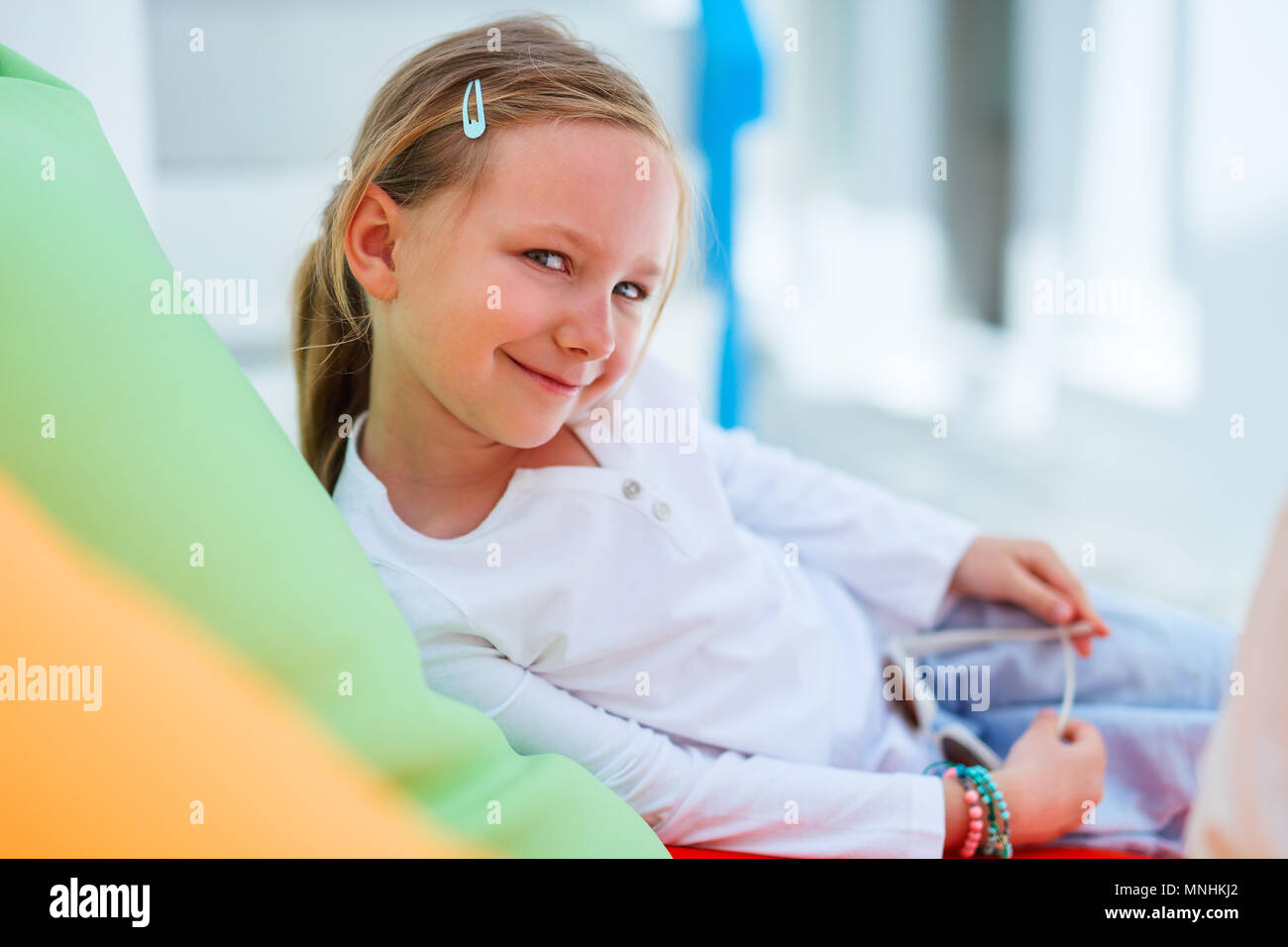 Adorable little girl on a colorful pillow in outdoor cafe on summer day - Stock Image