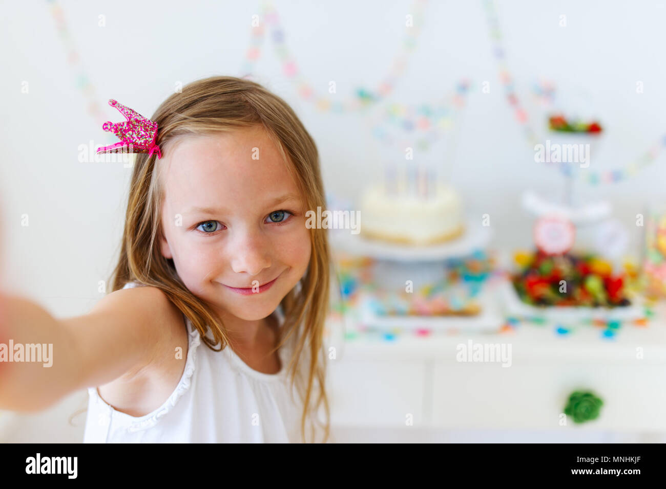 Adorable little girl with princess crown at kids birthday party taking selfie - Stock Image