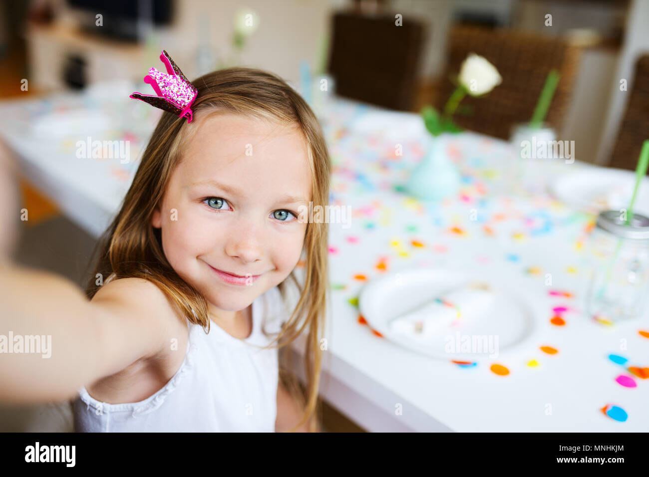 Adorable little girl with princess crown at kids birthday party making selfie - Stock Image