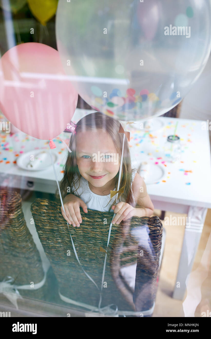 Adorable little girl with colorful balloons at kids birthday party looking through a window Stock Photo
