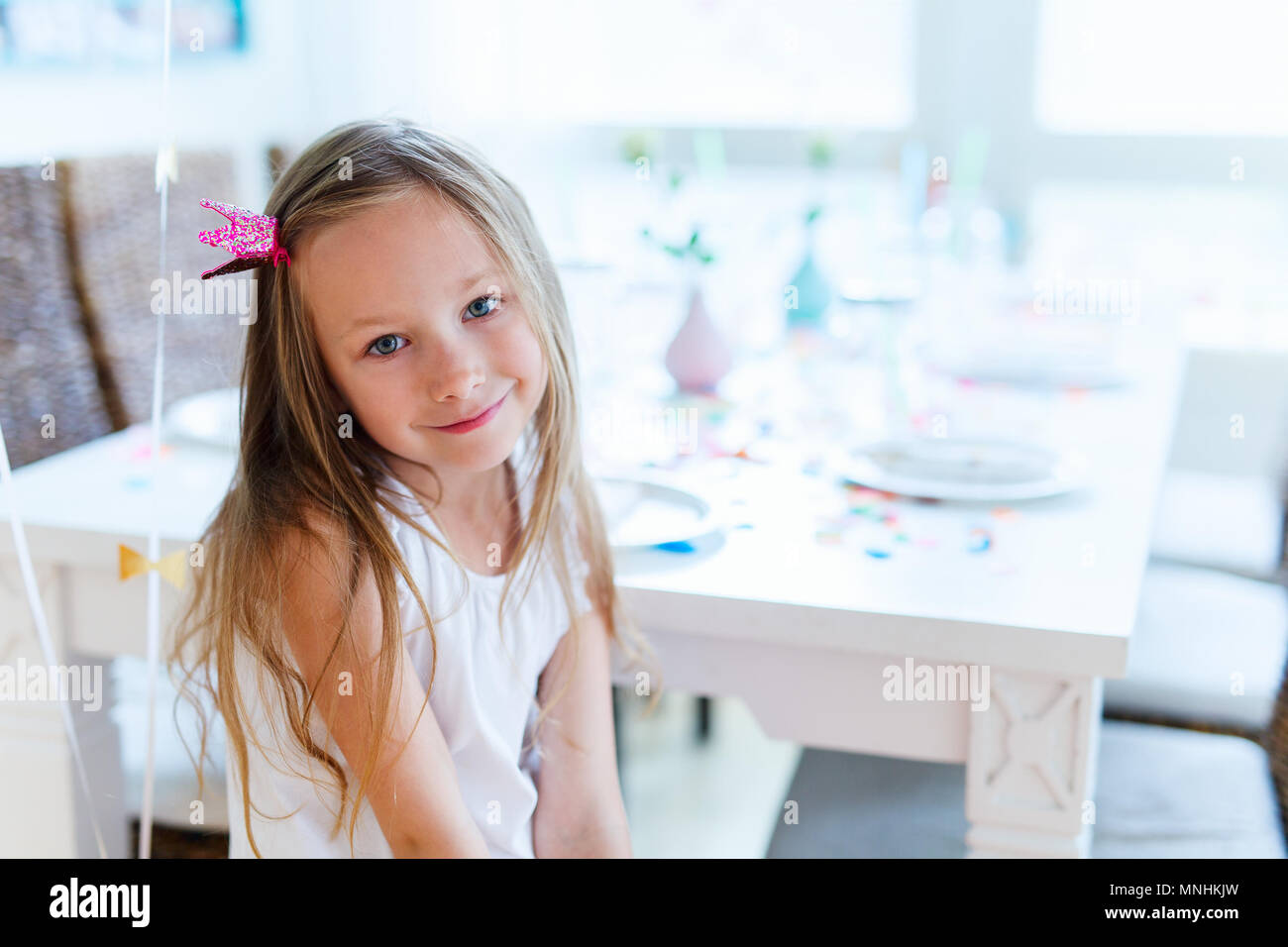 Adorable little girl with princess crown at kids birthday party - Stock Image