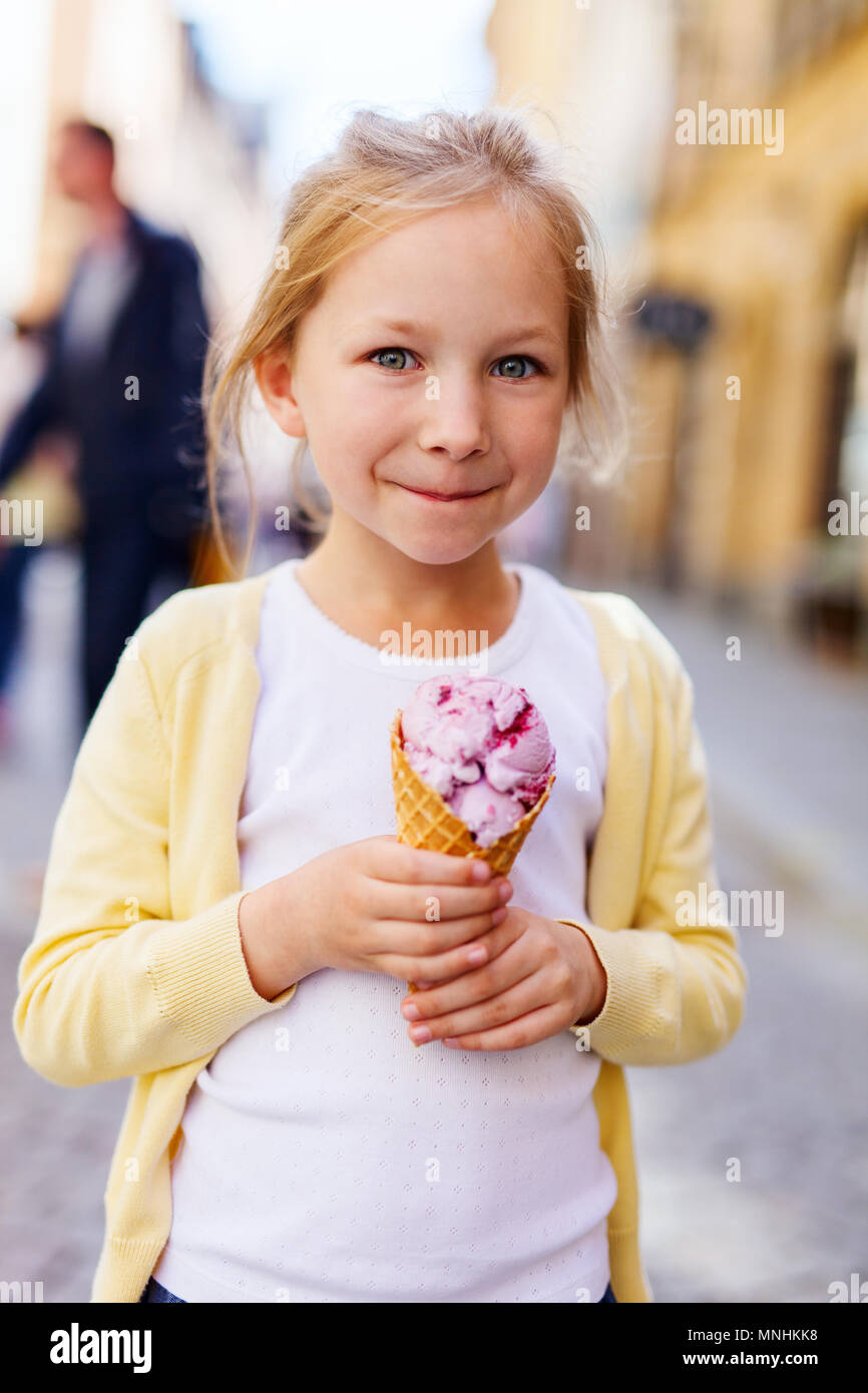 Adorable little girl eating ice cream in a fresh waffle cone