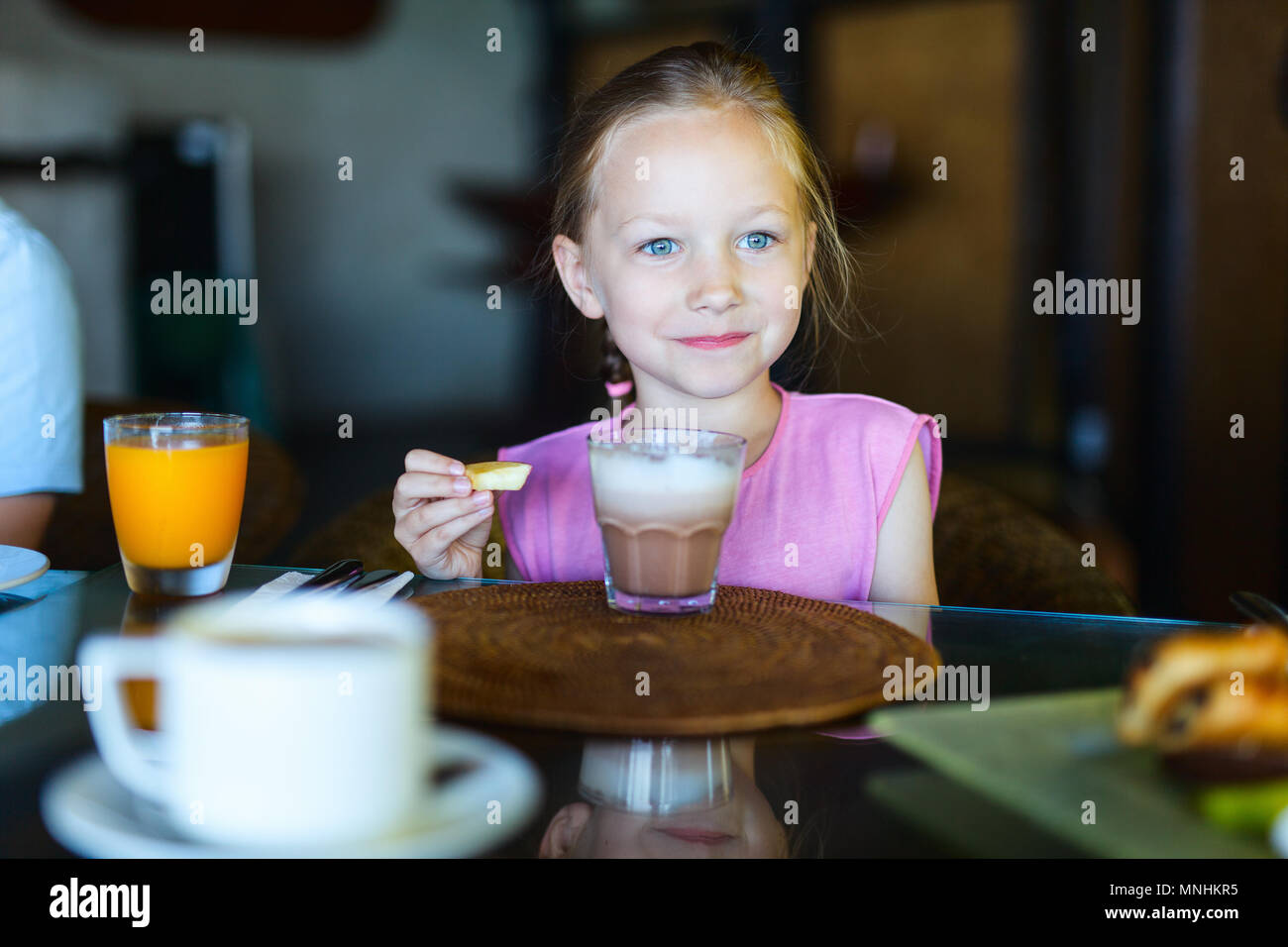 Adorable little girl in restaurant drinking hot chocolate - Stock Image